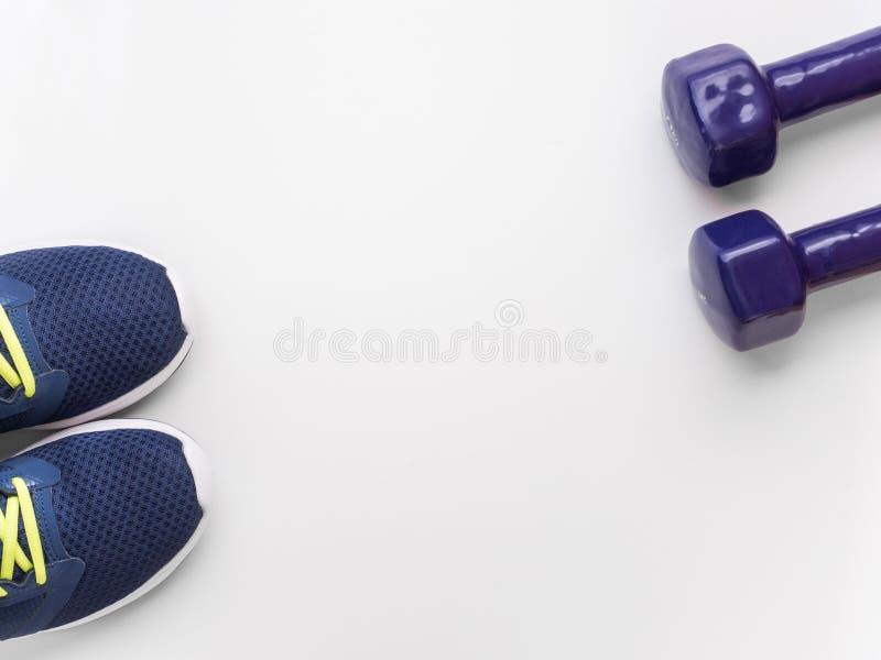 Deportes y concepto activo de la forma de vida Zapatillas deportivas púrpuras y dos pesas de gimnasia en el fondo blanco Endecha  imagen de archivo libre de regalías