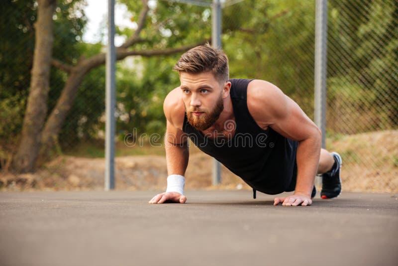 Deportista barbudo atractivo que hace pectorales al aire libre foto de archivo libre de regalías