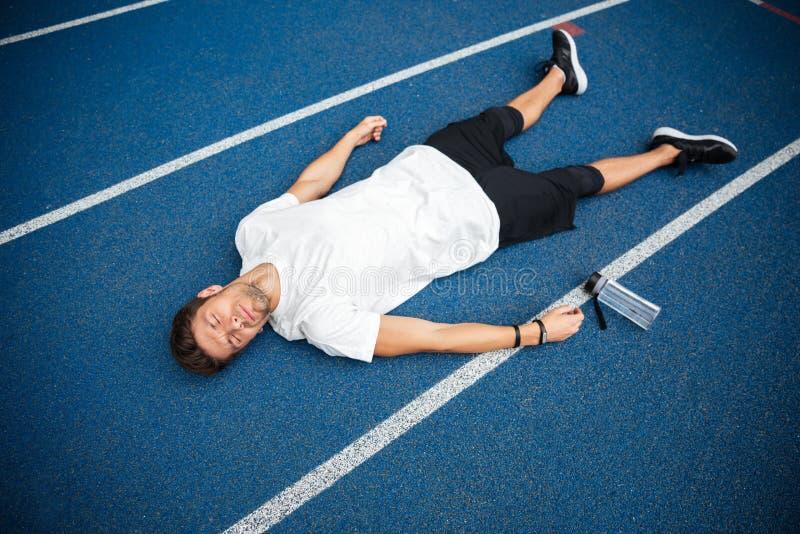Deportista cansado que miente en una pista con la botella de agua foto de archivo