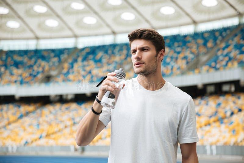 Deportista cansado que sostiene la botella de agua foto de archivo