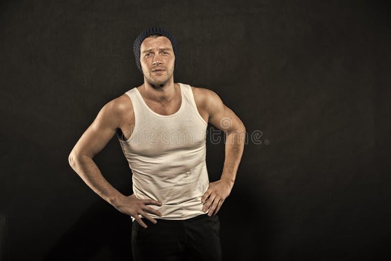 Deportista con confianza y carisma Soporte del hombre de la aptitud con las manos en caderas Machista en chaleco y sombrero de mo foto de archivo