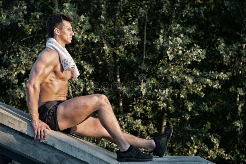 Deportista con el cuerpo muscular y toalla que se sienta en superficie concreta imágenes de archivo libres de regalías