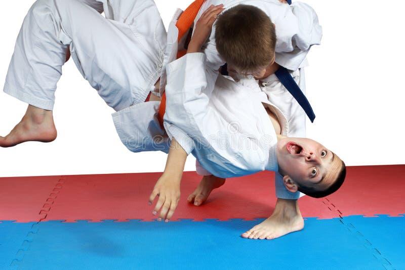 Deportista con una correa azul que hace el tiro de judo imagen de archivo libre de regalías