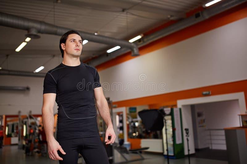 Deportista construido atlético joven muscular que se opone al pasillo del gimnasio foto de archivo libre de regalías