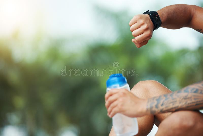 Deportista de la cosecha que comprueba el smartwatch al aire libre fotografía de archivo libre de regalías