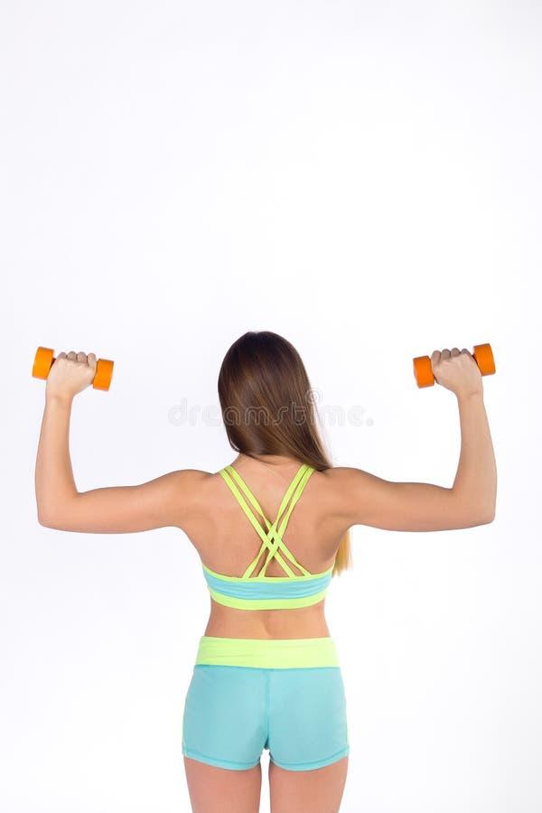 Deportista en ejercicios de la ropa de deportes con pesas de gimnasia imagenes de archivo