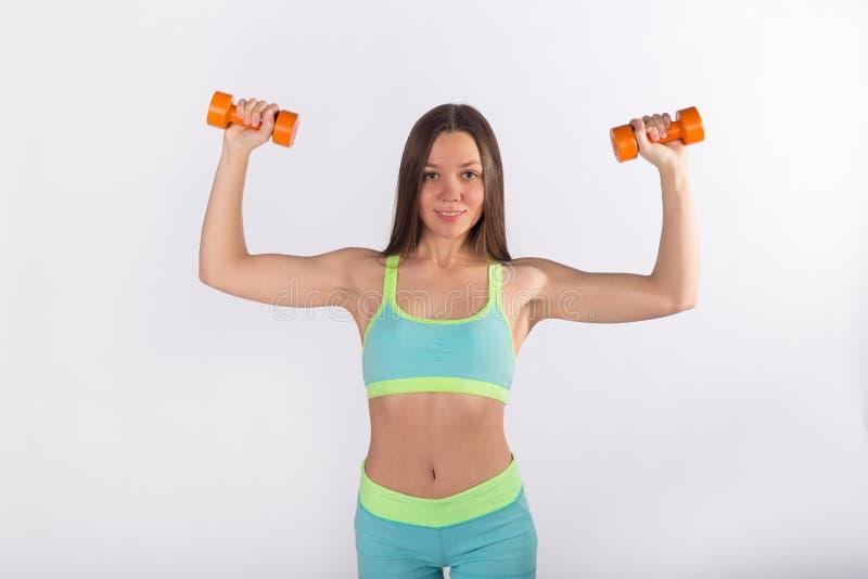 Deportista en ejercicios de la ropa de deportes con pesas de gimnasia foto de archivo