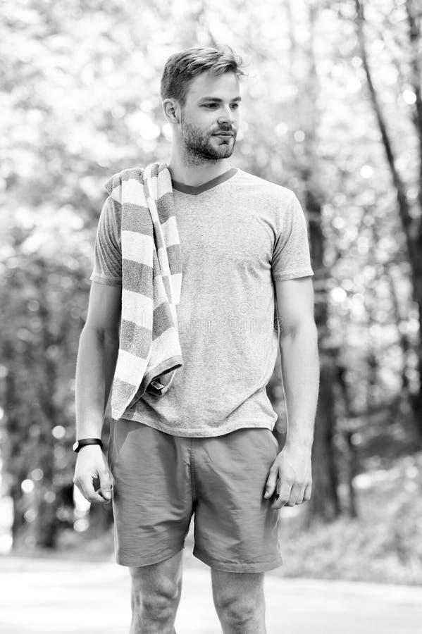 Deportista enseguida después del entrenamiento Hombre con la toalla en paisaje natural Sudoroso y cansado Tiempo y vacaciones de  imagen de archivo