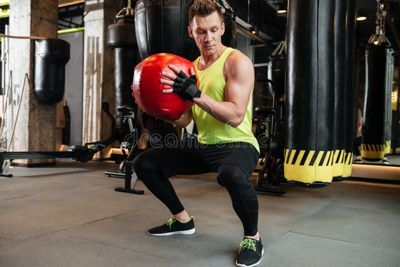 Deportista fuerte del ajuste que hace posiciones en cuclillas con la bola del peso imágenes de archivo libres de regalías