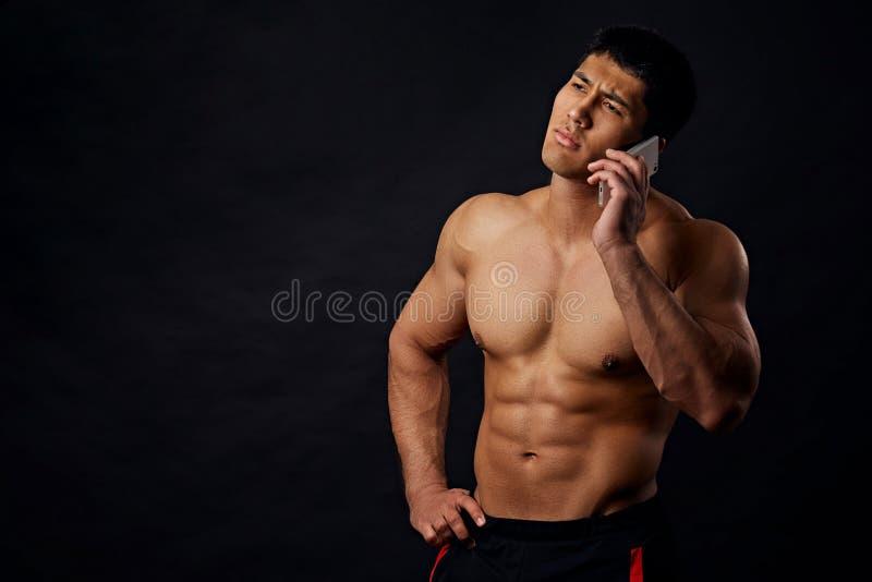 Deportista impresionante atractivo que tiene una conversación sobre el teléfono imagen de archivo libre de regalías