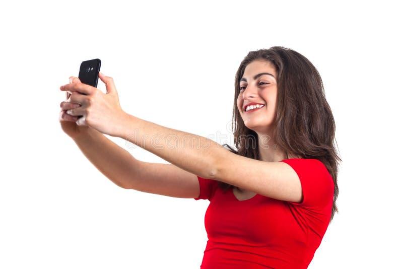 Deportista joven atractiva alegre que usa el teléfono móvil sobre wh foto de archivo