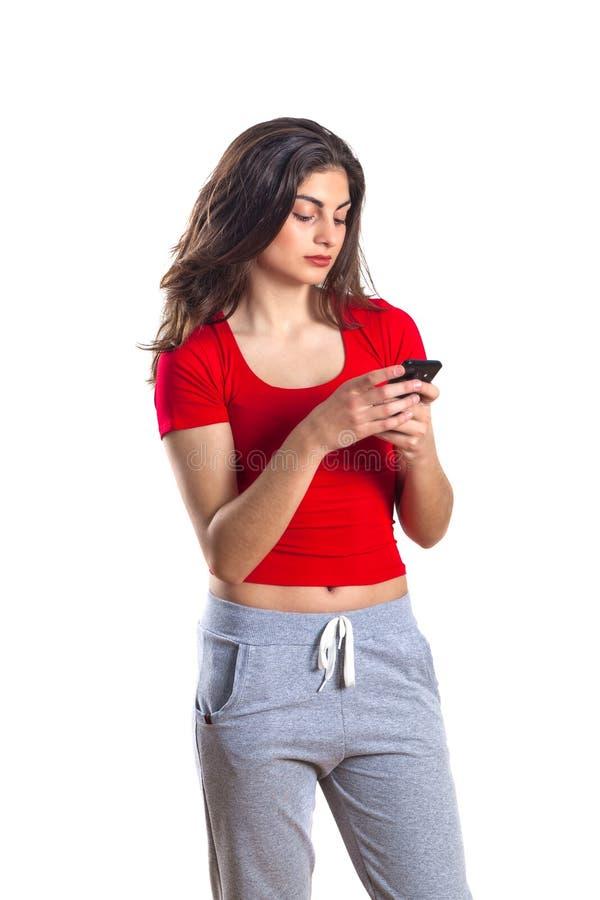 Deportista joven atractiva alegre que usa el teléfono móvil sobre wh imágenes de archivo libres de regalías