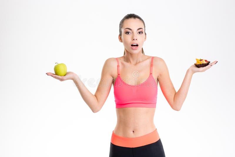 Deportista joven emocionada confusa que elige entre las frutas y los dulces imágenes de archivo libres de regalías