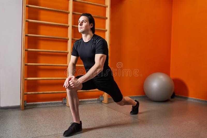 Deportista joven en el sportwear negro que estira la pierna antes de entrenamiento del gimnasio contra la pared anaranjada brilla imagen de archivo