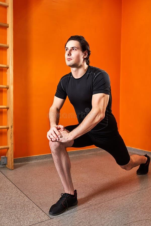 Deportista joven en el sportwear negro que estira la pierna antes de entrenamiento del gimnasio contra la pared anaranjada brilla fotografía de archivo libre de regalías