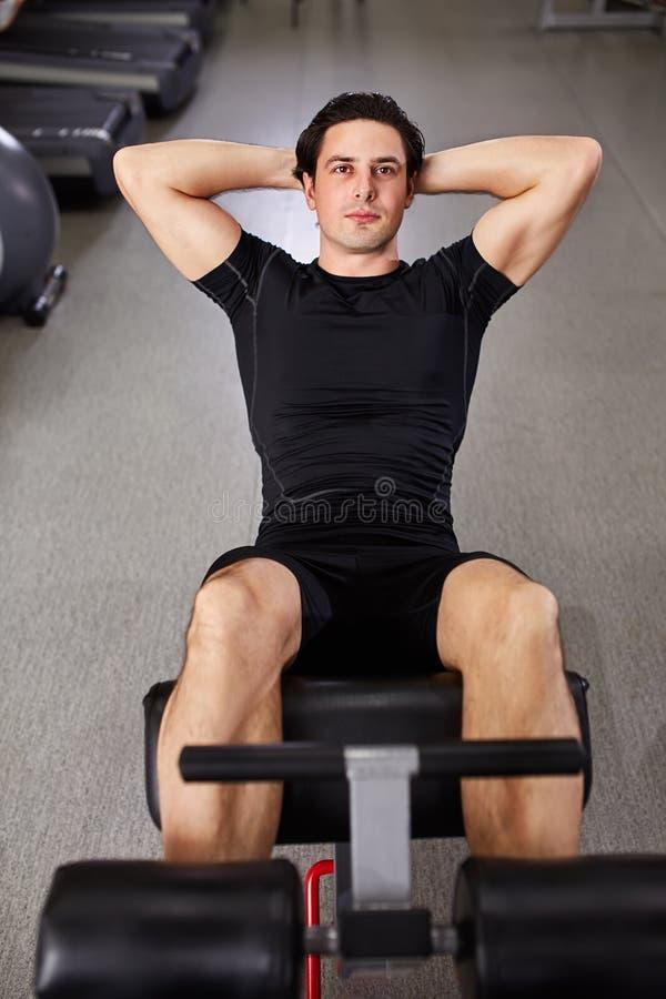 Deportista joven en el sportwear negro que hace ejercicios abdominales en gimnasio imagenes de archivo