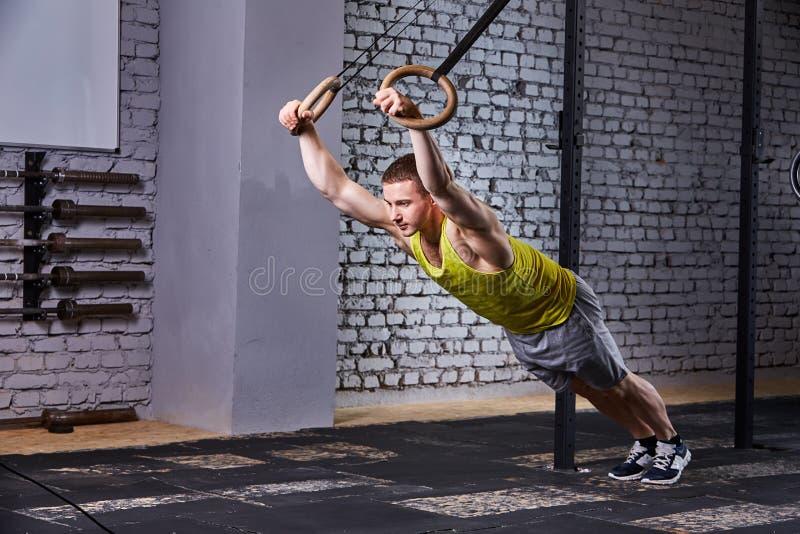 Deportista joven en el sportwear que ejercita con los anillos gimnásticos en gimnasio contra la pared de ladrillo fotos de archivo libres de regalías