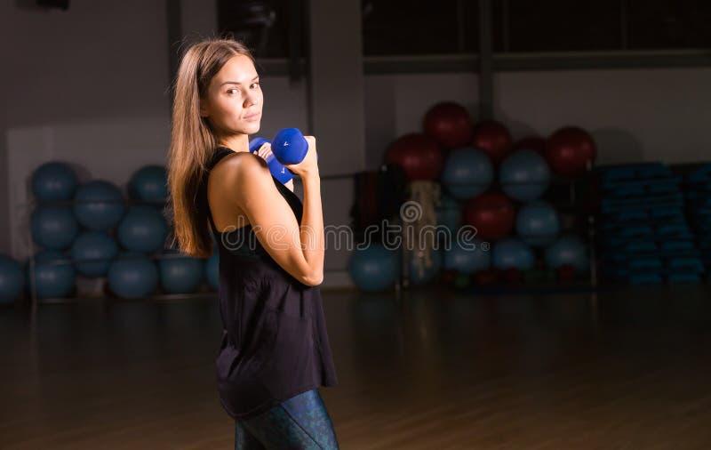 Deportista joven hermosa que hace ejercicios con pesas de gimnasia en gimnasio fotografía de archivo