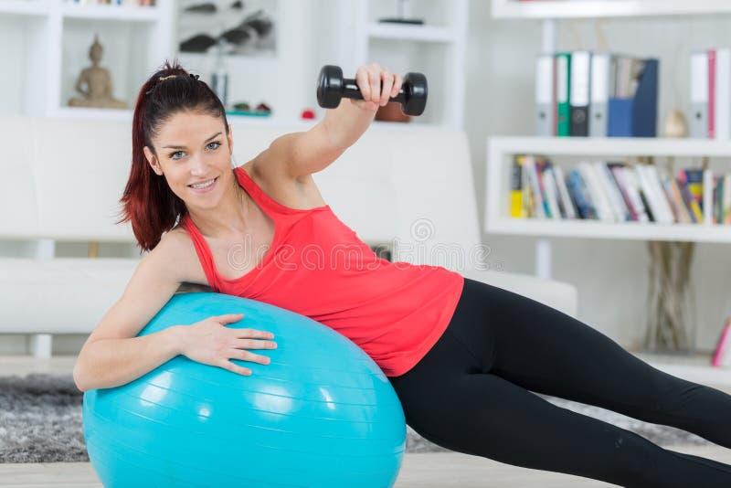 Deportista joven que hace ejercicios con la bola y pesas de gimnasia imagen de archivo