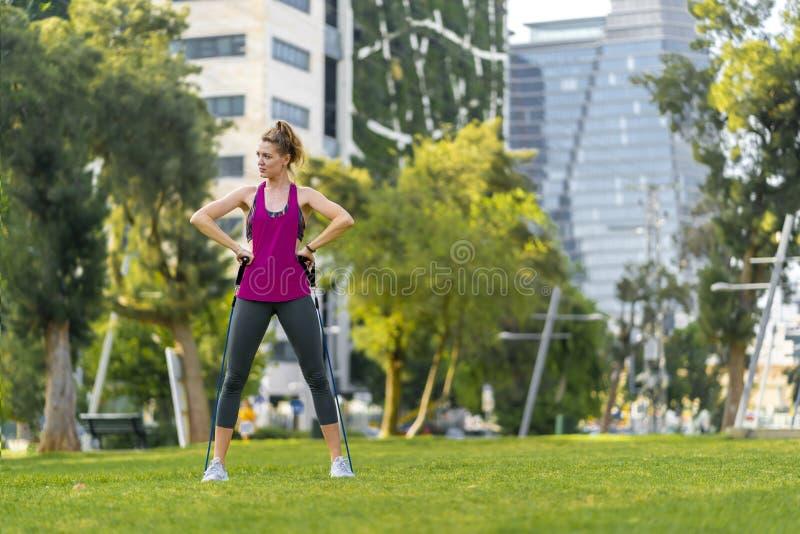 Deportista joven que realiza ejercicios en la hierba en una ciudad imagenes de archivo