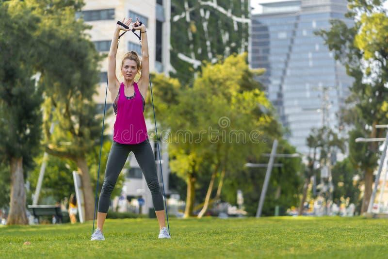 Deportista joven que realiza ejercicios en la hierba en una ciudad fotos de archivo