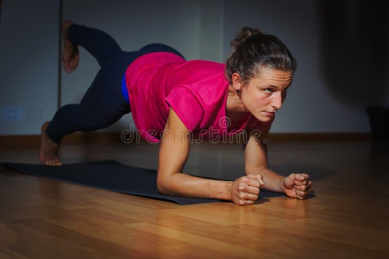 Deportista joven seria que hace el ejercicio en gimnasio - aptitud del tablón, imagen de archivo