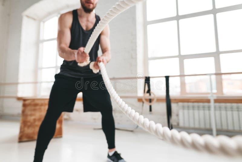 Deportista muscular que hace ejercicios cruzados con las cuerdas en gimnasio del entrenamiento imagen de archivo libre de regalías