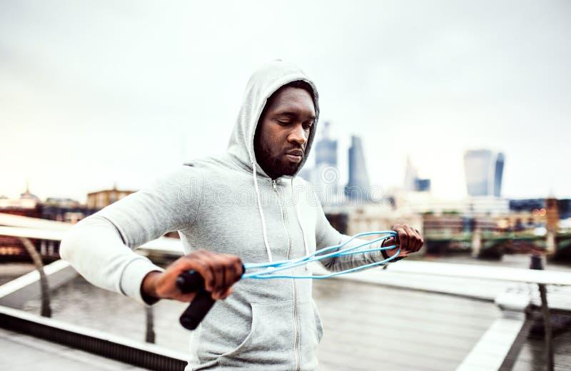 Deportista negro activo joven con la cuerda que salta en una ciudad, sudadera con capucha que lleva imagen de archivo
