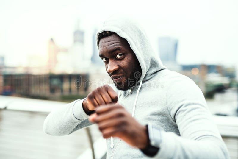 Deportista negro activo joven en la posición en una ciudad, sudadera con capucha que lleva del boxeo fotos de archivo