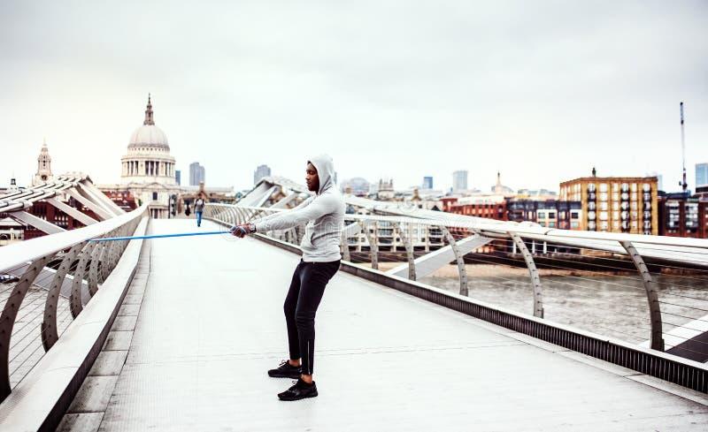 Deportista negro activo joven que ejercita con las gomas elásticos en Londres fotos de archivo
