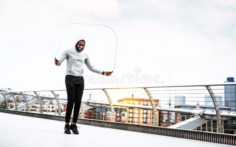 Deportista negro activo joven que salta con una cuerda en una ciudad, sudadera con capucha que lleva imágenes de archivo libres de regalías