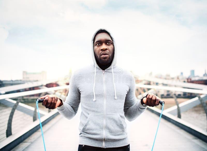 Deportista negro activo joven que salta con una cuerda en una ciudad, sudadera con capucha que lleva fotografía de archivo libre de regalías