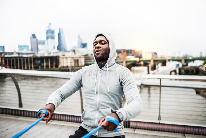 Deportista negro joven que ejercita con las gomas elásticos en Londres foto de archivo