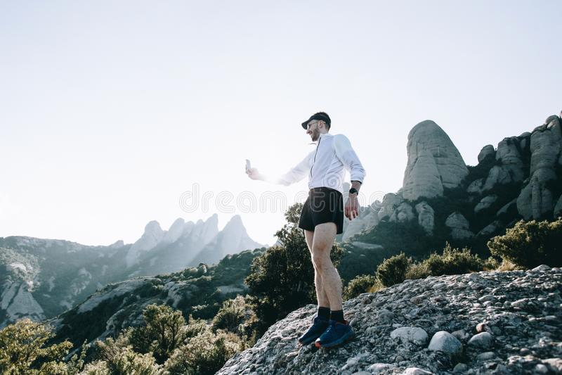 Deportista o atleta con smartphone en la montaña fotos de archivo