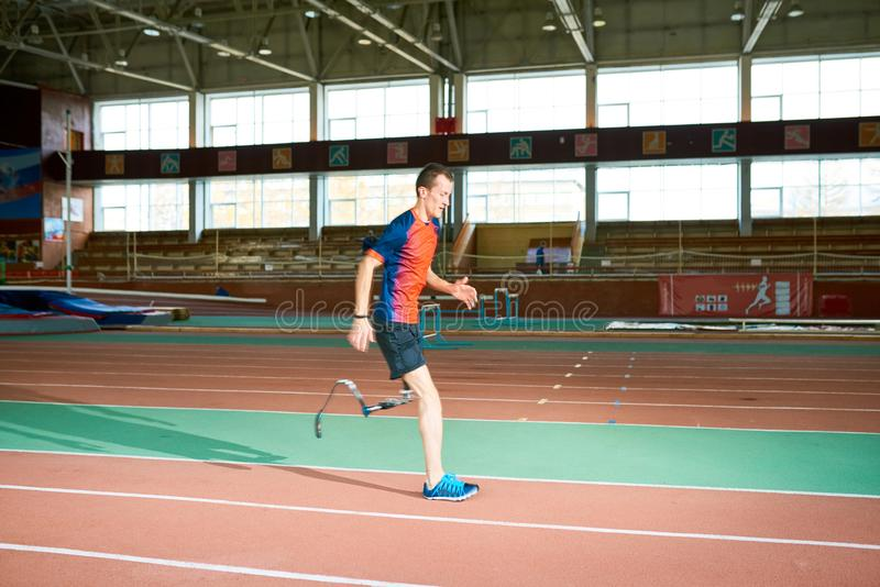 Deportista perjudicado que corre en pista foto de archivo libre de regalías