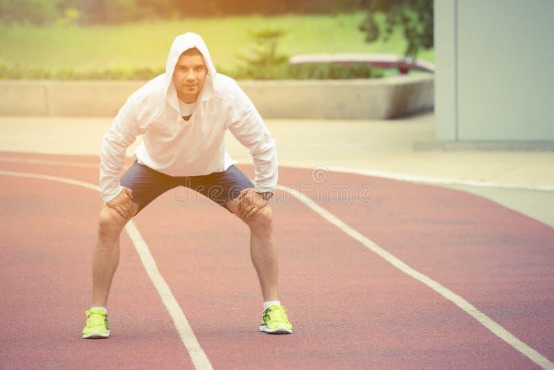 Deportista que descansa sobre la pista corriente al aire libre foto de archivo