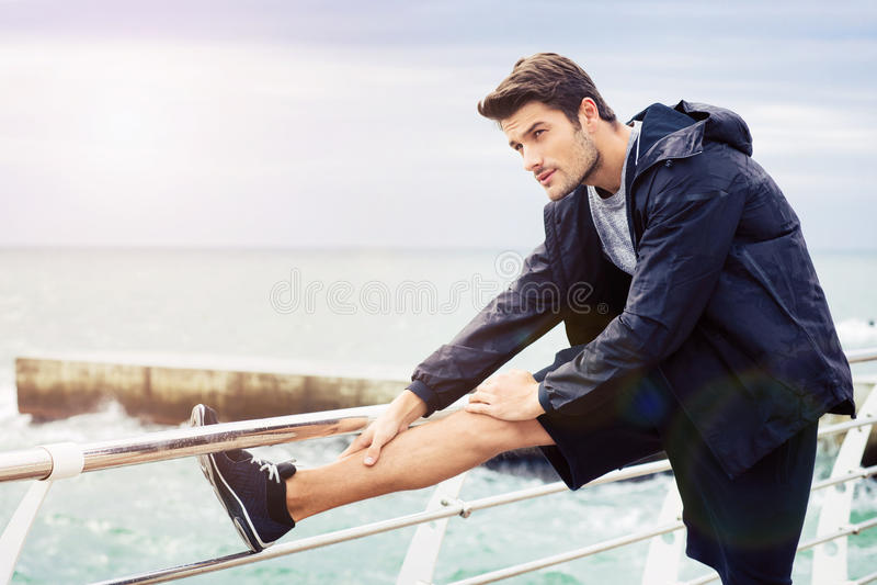Deportista que estira las piernas al aire libre foto de archivo