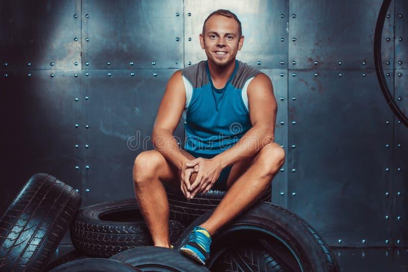 Deportista que se sienta en la máquina del neumático Concepto de CrossFit, de salud y de fuerza fotos de archivo libres de regalías