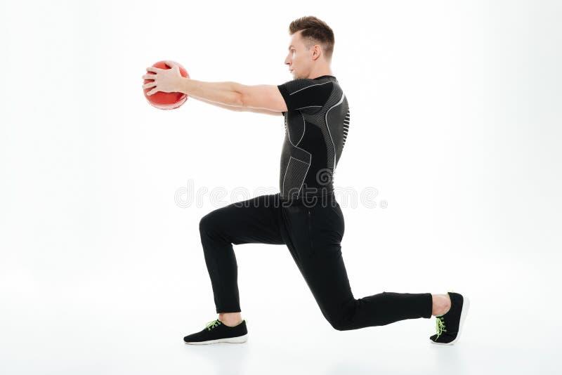 Deportista sano joven que hace posiciones en cuclillas con la bola del peso imagen de archivo