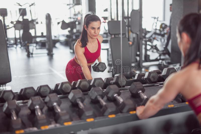 Deportista seria que se resuelve con pesa de gimnasia fotografía de archivo