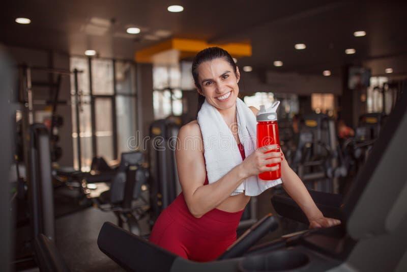 Deportista sonriente con la botella en la rueda de ardilla foto de archivo libre de regalías