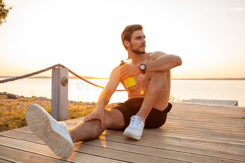 Deportista sonriente joven hermoso que sienta y que sostiene la botella de agua al aire libre fotos de archivo libres de regalías