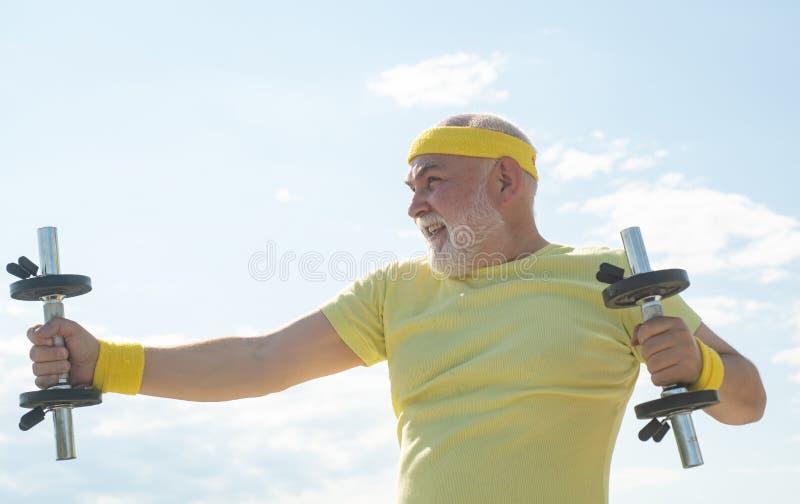 Deportista superior en el centro deportivo. Pesas de gimnasia de elevaci?n. Atención de la salud. Hombre mayor haciendo ejercicio fotos de archivo