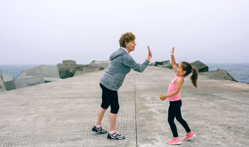 Deportista y niña mayores altos cinco imagen de archivo