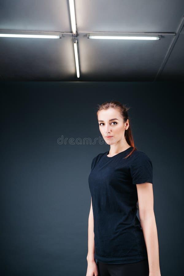 Deportivo-mirada de la muchacha en una camiseta negra y polainas fotos de archivo