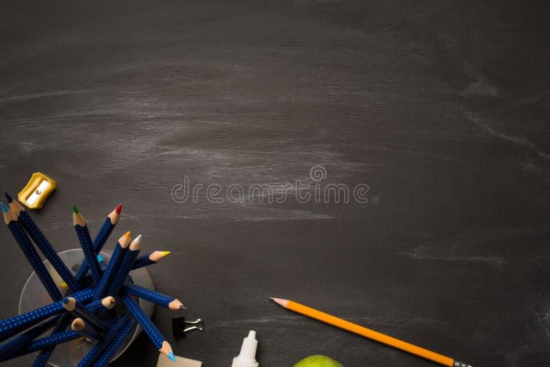 Deposite o recipiente com lápis e materiais de escritório coloridos na placa de giz preta foto de stock royalty free