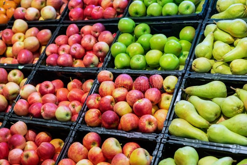 Deposito del supermercato della drogheria Scaffali con varietà di pere e di mele mature fresche orgnaic differenti Servizio della immagine stock