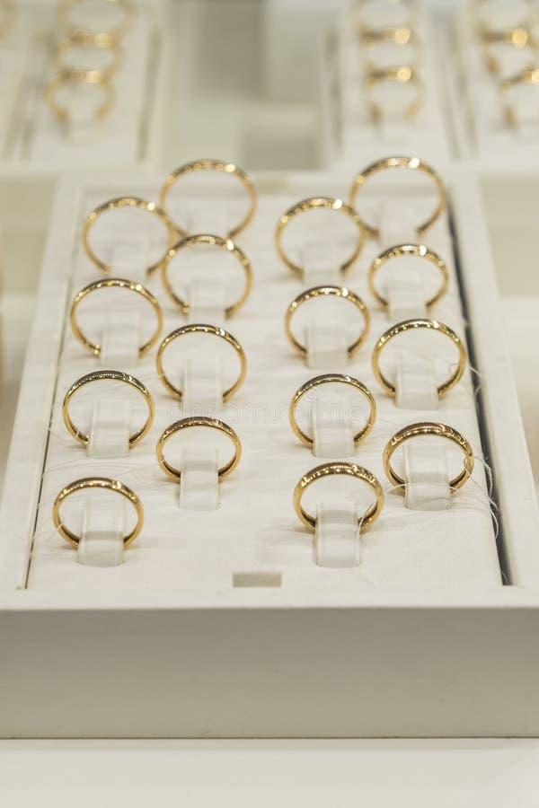 Deposito dorato degli anelli Anelli di oro di nozze sulla vetrina Nozze Ring Set modificato Foto verticale fotografie stock libere da diritti