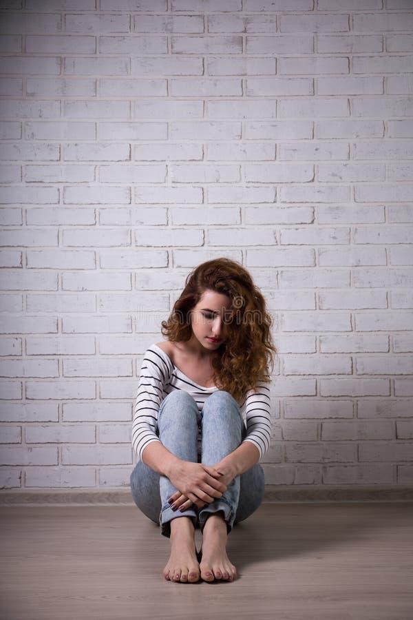 Depresja i samotność - smutny młodej kobiety obsiadanie na podłoga fotografia stock