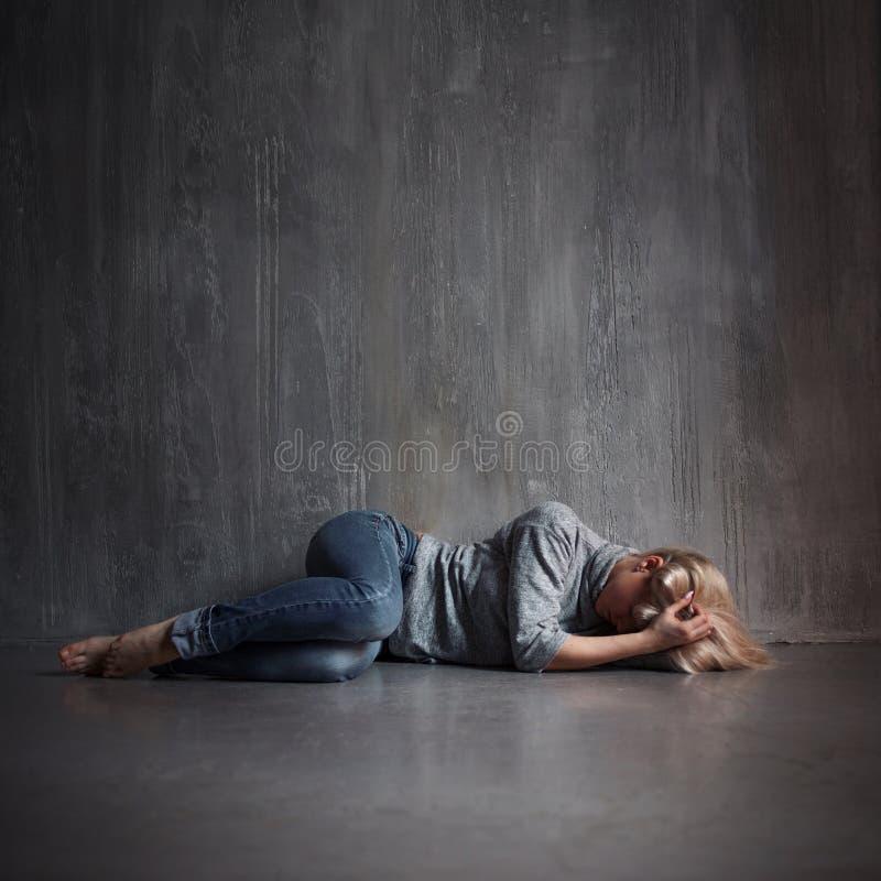 Depresja Młodej kobiety lying on the beach na podłogowego nakrycia głowie z rękami zdjęcie stock